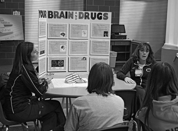 """Two women nurses sit at a table talking to two teenagers during the Drugs 101 program. The teens have their backs to the camera. On the table is a trifold display board with the words: """"Your Brain and Drugs."""" The nurse on the right is talking. Both nurses are wearing sweat suits with the Penn State logo on them."""