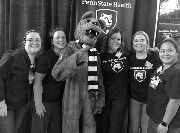 The Penn State Nittany Lion poses with his thumb up and a bandage on his arm at the Pennsylvania Farm Show. He is standing with five women who are community health nurses at Penn State Health Milton S. Hershey Medical Center. Behind them is a Penn State Health banner and a curtain.