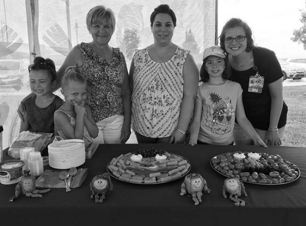 Three women smile at a table with three young girls at the Farmers Market in Hershey in 2017. Two trays of vegetables are on the table in front of them with four dolls shaped as fruits and vegetables. Behind them is a thin curtain. A row of parked cars is on the right.