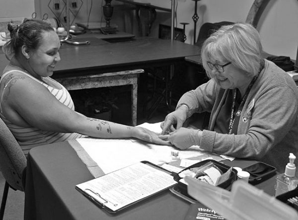 A woman community health nurse from Hershey Medical Center does a finger stick test on a woman at a food pantry. The nurse is wearing glasses, a sweater, scrubs, a Penn State Health lanyard and rubber gloves. The client is smiling as she stretches out her arm on a paper towel. She is wearing a striped tank top and has tattoos on her back and arm. The table has a clipboard, phone and a plastic container on it. Behind them are tables with various household items on them.