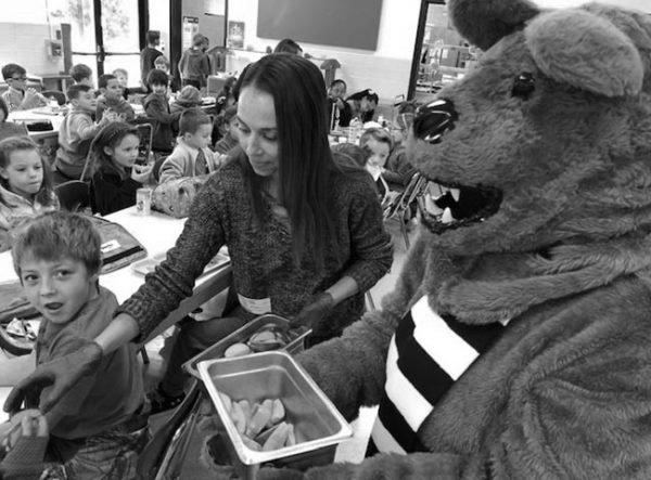 A woman hands out apple slices in a crowded elementary school cafeteria during a Penn State PRO Wellness Apple Crunch event. The Penn State Nittany Lion mascot stands next to her holding a bin of apple slices. The woman is wearing a sweater and has plastic gloves on her hands. A young boy looks at the camera with a surprised expression on his face.