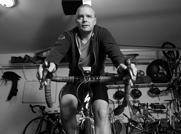 Tim Card of Mount Joy, Pa., the first patient at Penn State Cancer Institute to receive CAR-T therapy, rides on a stationary bike in his garage. He is wearing a sweatshirt, T-shirt and bike shorts. Behind him is a shelf filled with sports equipment and bike helmets on the wall. A garage door opener and a light are above him.