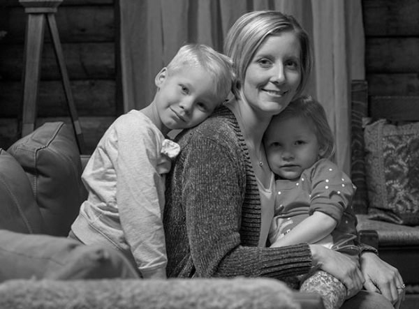 Krista Carroll of Shippensburg smiles with her children Madden, 6, and Jillian, 3, in a black and white portrait. They are sitting on a couch. Krista is wearing a sweater and casual top. Madden is leaning his head on his mother's back and is wearing a long-sleeved shirt. Jillian is sitting in her mother's lap and wearing a polka-dotted shirt. Behind them is a log cabin wall, a curtain and pillows on a chair.