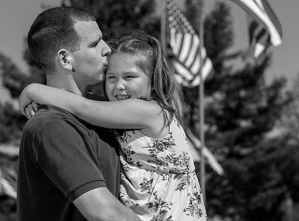 Paul Brennan kisses his daughter Lilly's forehead as he holds her in his arms. They are standing in front of a row of American flags. He has short hair and is wearing a polo shirt. She has shoulder-length hair, is wearing a flowered dress and is smiling. Behind them are trees.