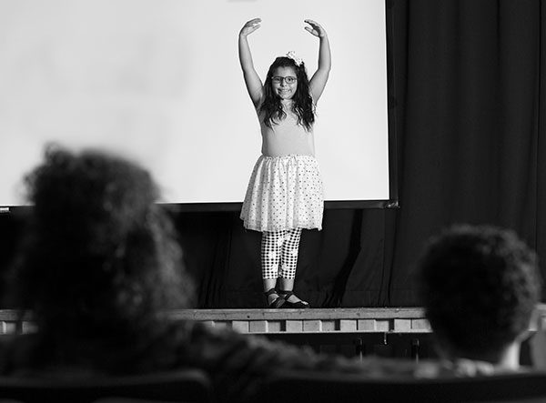 Gabriella Asadi dances on a stage, smiling at her mother and brother. The backs of their heads are shown from behind as they sit in their audience seats.