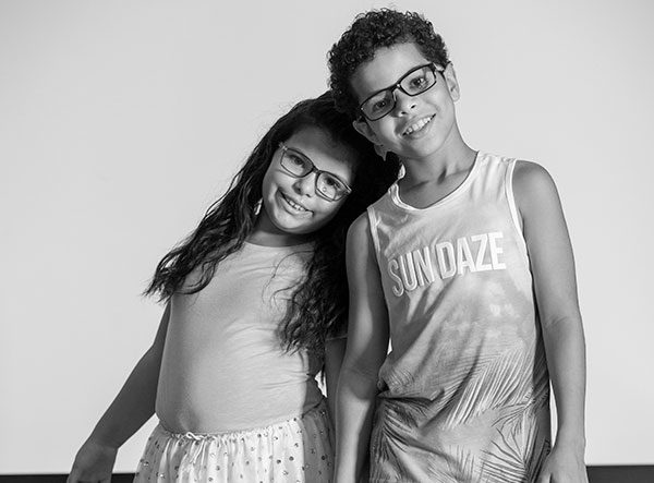 Gabriella Asadi leans on the shoulder of her brother, Xavier. She has long hair and wears a dance skirt and top. Xavier has short curly hair and wears a tank top. Both wear eye glasses they got through Vision to Learn's mobile eye clinic when it came to Steelton-Highspire Elementary School last summer.