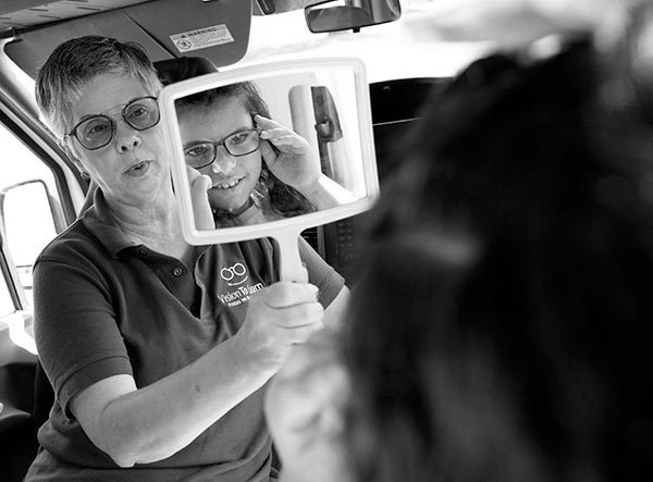 Nancy Mesko, optician with Vision to Learn, holds a mirror in front of Gabriella, whose image in seen in the mirror as she checks how a pair of glasses look on her face. Mesko has short hair and glasses and wears a T-shirt with a Vision to Learn logo on it.