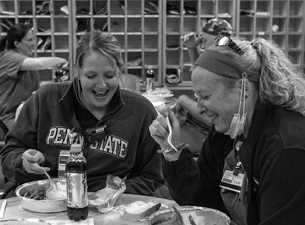 Jennifer Gramley, nurse practitioner, and Kate Perkins, registered nurse, sit at a round table, eating ham, potatoes and string beans from foil food containers. Gramley wears a Penn State pullover and has her hair in a ponytail. Perkins has a ponytail and wears a jacket over scrubs and a face mask under her chin while she eats.