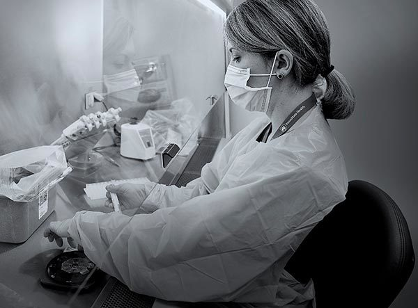 A woman medical laboratory scientist at Penn State Health Milton S. Hershey Medical Center holds a test tube as she performs a test. On the counter in front of her is a container lined in plastic and lab equipment. She is wearing plastic scrubs, a face mask and a lanyard around her neck. She has short hair pulled into a ponytail.