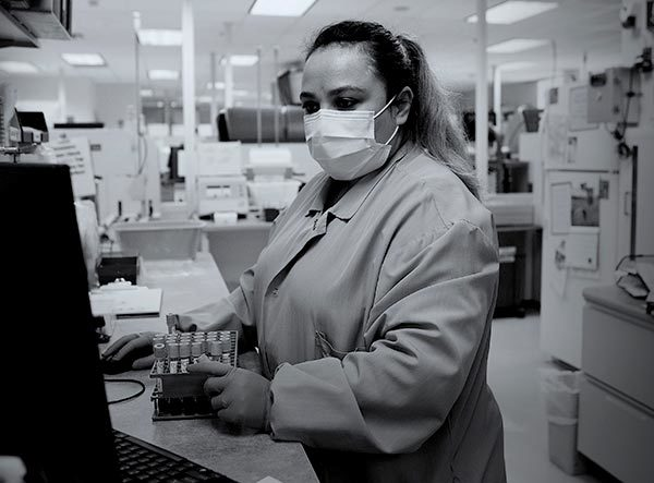 A woman medical laboratory scientist at Penn State Health St. Joseph touches a box of test tubes as she looks at a computer screen. She is wearing scrubs and a face mask and has long hair in a ponytail. Behind her are lab equipment and lights.
