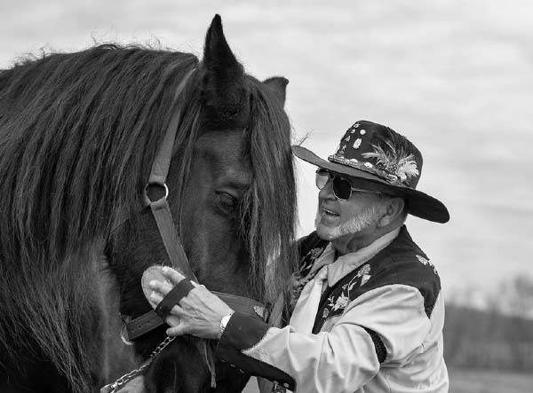 A man smiles as he holds the harness of a horse. The man has a beard and is wearing sunglasses, a cowboy hat with a feather in it, a flowered vest and a long-sleeved shirt. The horse's head is visible with a long forelock hanging over its eyes and a harness on the right side of its head.