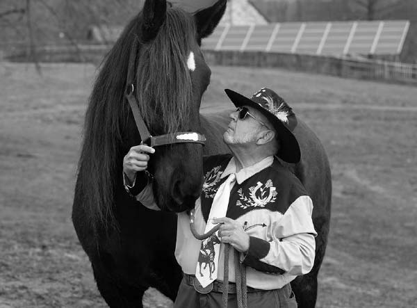 A man looks up at a horse and holds its harness in his right hand and a rope in his left hand. The man has a beard and is wearing sunglasses, a cowboy hat with a feather in it, a flowered vest and a long-sleeved shirt. The horse's entire body is visible. It has a spot on its forehead, and its forelock hangs over its eyes. Behind them a fenced arena and solar panels are visible.