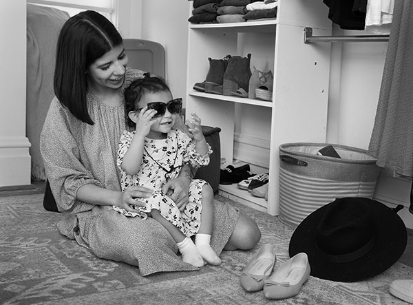 Alyssa Acevedo, who has shoulder-length hair and wears a long-sleeve dress, sits on her bedroom floor with her toddler daughter, who wears a print dress and sunglasses, on her lap. Shoes and clothes surround them on closet shelves and on the floor.