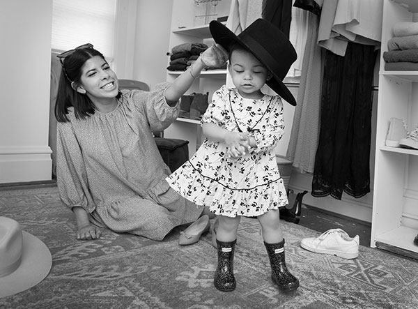 Alyssa Acevedo, who has shoulder-length hair and wears a long-sleeve dress, sits on her bedroom floor and smiles as she put a large felt hat on her toddler daughter's head. Izzy, who wears a print dress and boots, clasps her hands together. Shoes and clothes surround them on closet shelves and on the floor.