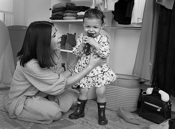 Alyssa Acevedo, who has shoulder-length hair and wears a long-sleeve dress, hugs her toddler daughter, who stands in front of her. Izzy wears a print dress and chews on sunglasses. Shoes and clothes surround them on closet shelves and on the floor.